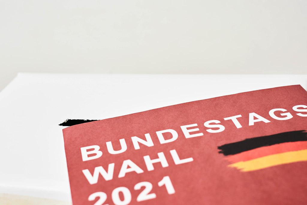 """Nahaufnahme eines rotes Zettels mit der Schrift """"Bundestagswahl 2021"""" und der deutschen Flagge"""