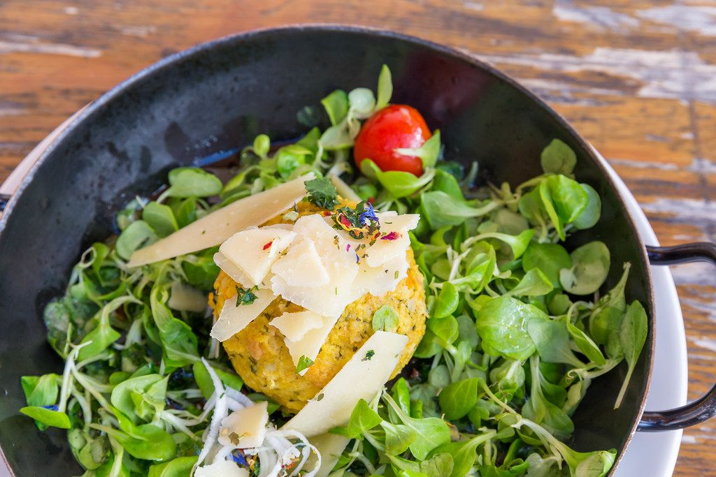 Nahaufnahme: Kürbisknödel in der Pfanne mit Feldsalat und Parmesan bei der Dauerstoa Alm