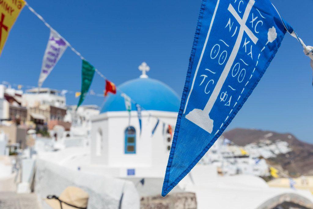 Nahaufnahme von blauer Fahne auf Santorin mit blauer Kuppel einer Kirche im Hintergrund