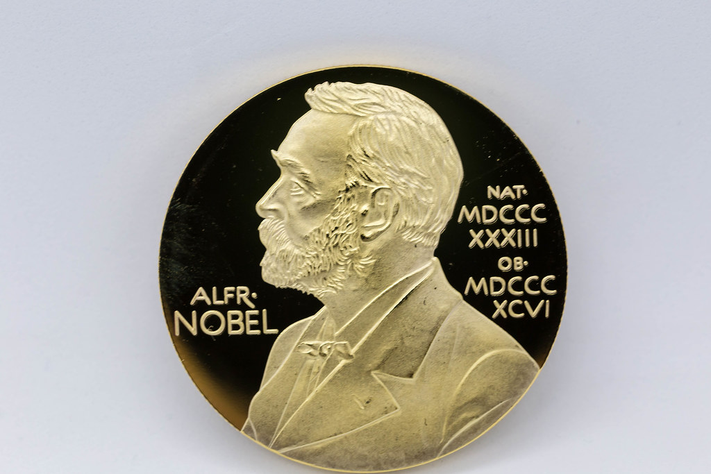 Nahaufnahme von Goldmedaille mit Porträt von Alfred Nobel vor weißem Hintergrund