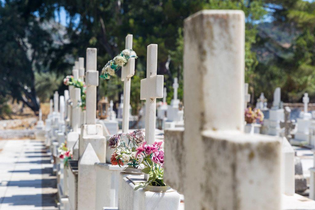 Nahaufnahme von Marmorgräbern mit Kreuzen und Blumen: Agios Charalampos Friedhof auf Naxos