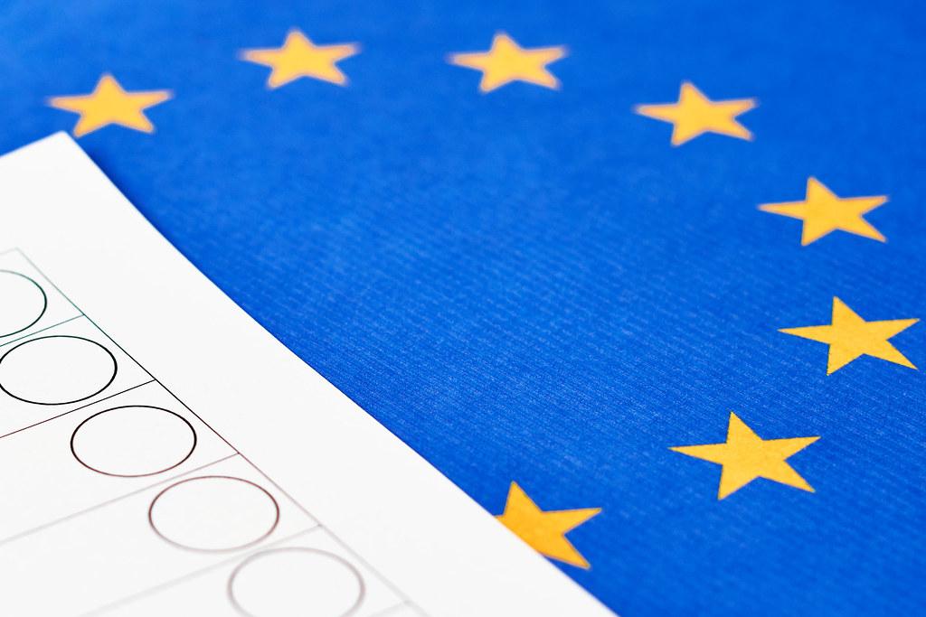 Nahaufnahme von Muster-Stimmzettel ohne Namen und EU-Flagge: Wahl in Europa
