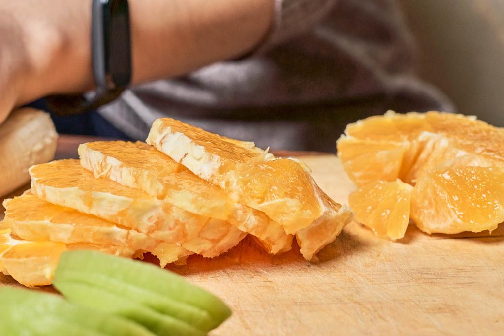 Nahaufnahme von Orangenscheiben auf einem Holzbrett mit Mann, der im Hintergrund schneidet