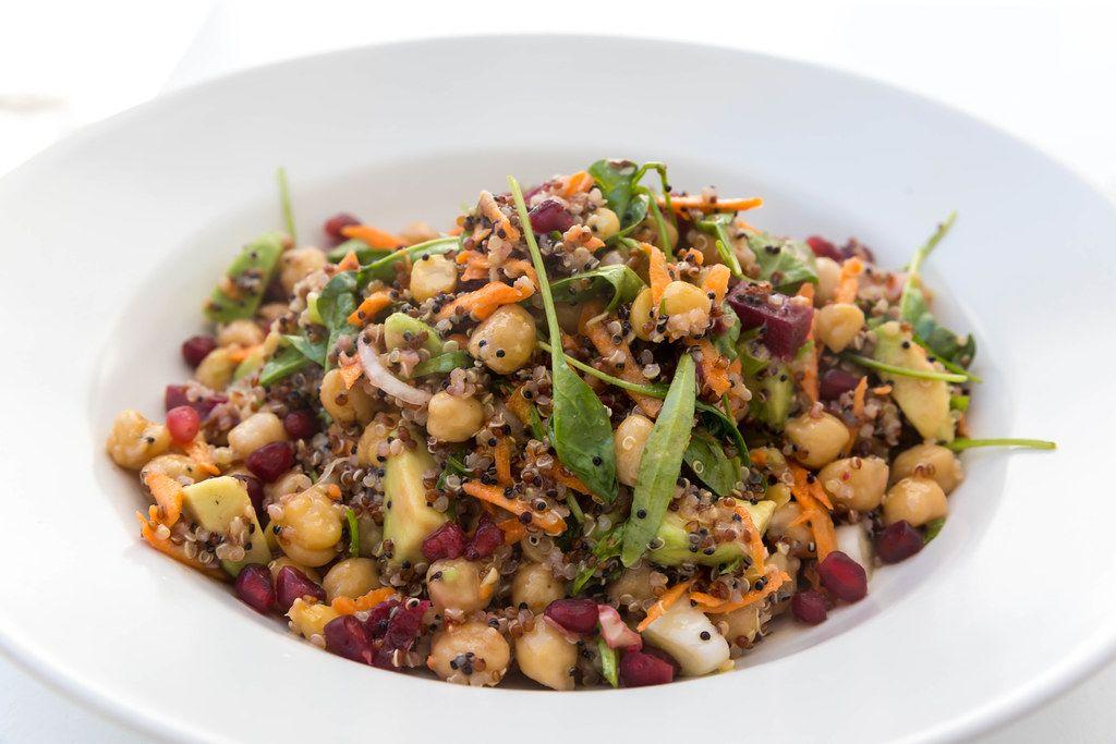 Nahaufnahme von weißem Teller mit Kichererbsen, Avocado, Quinoa, Gemüse. Vegan essen