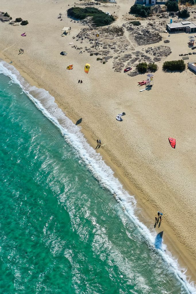 Naxos: drone photo of uncrowded sandy beach of Mikri Vigla with windsurfers resting and flying kites
