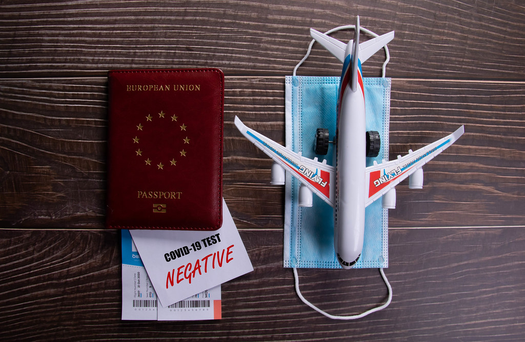 Negative Covid-19 test card with passport, face mask and airplane on wooden table