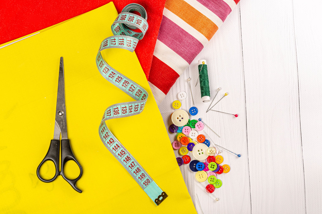 New fabrics with scissors, pins, measuring tape and buttons on a white wooden background
