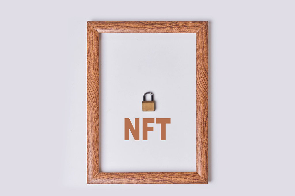 NFT digital crypto art in wooden frame. Non-fungible token cryptocurrency
