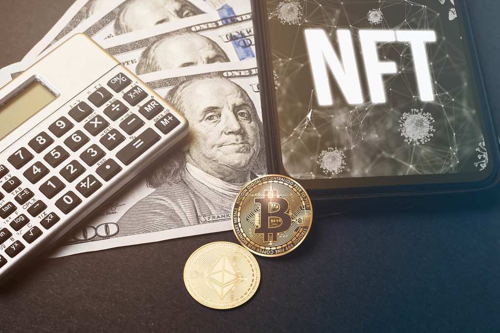 NFT - on the mobile phone screen, calculator, USD dollar bills, bitcoin and ethereum crypto coins on the table