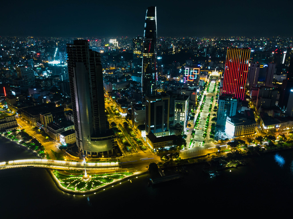 Night Drone Photo of Nguyen Hue Walking Street next to Bitexco Financial Tower and Saigon One Tower in District 1 in Ho Chi Minh City, Vietnam