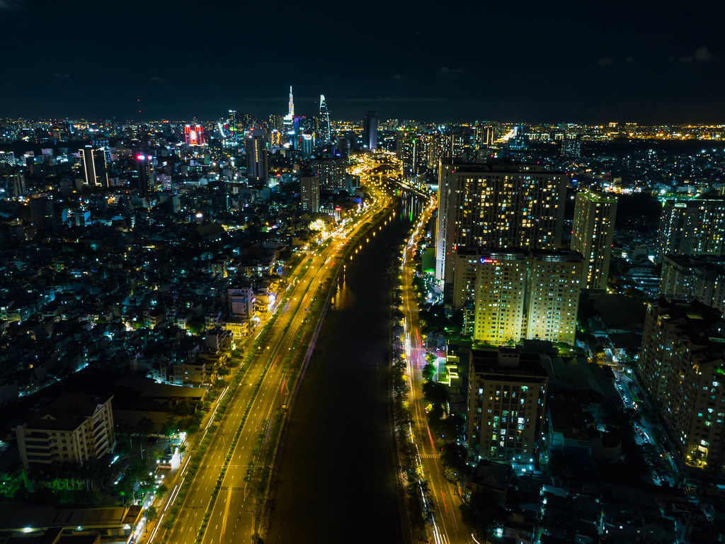 Night Drone Photo of Saigon River between District 1 and District 4 and the Skyline with Bitexco Financial Tower and Lanmark 81 in Ho Chi Minh City, Vietnam