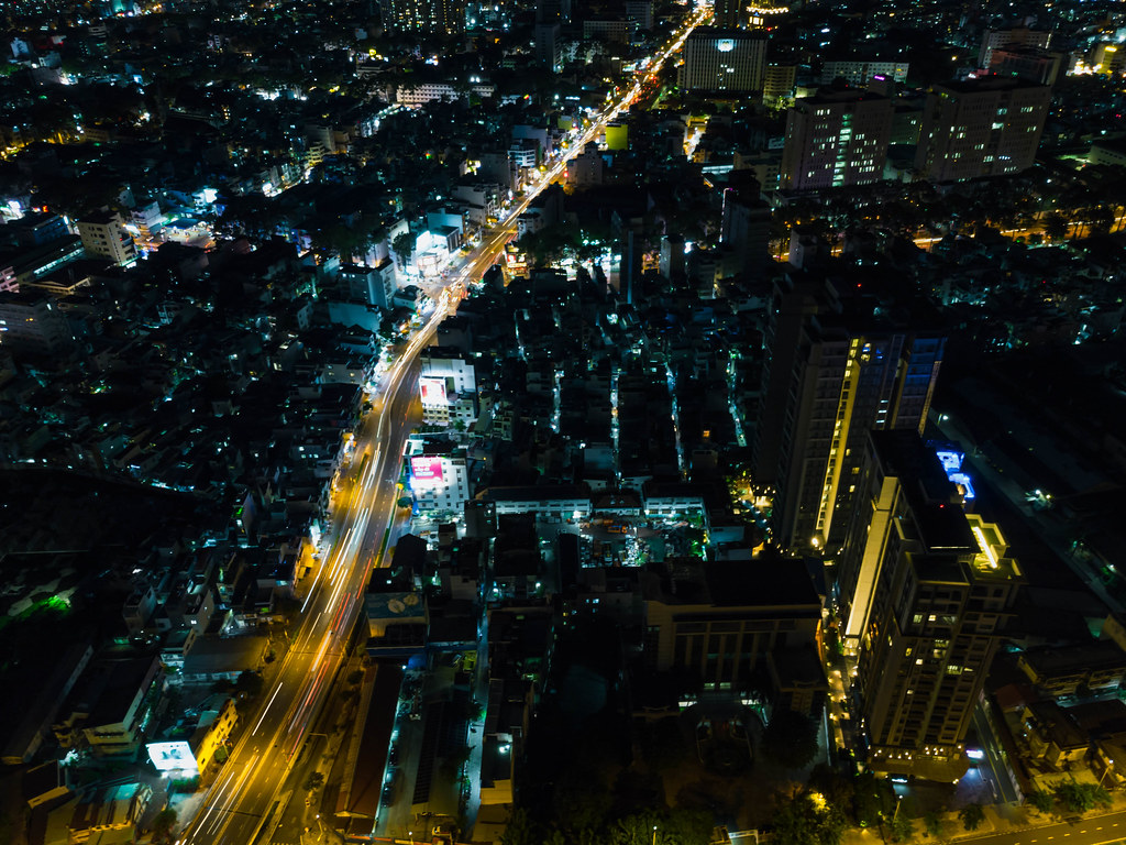 Night Drone Photo with Traffic Light Streaks with many Buiildings and Houses from above in District 1 in Ho Chi Minh City, Vietnam