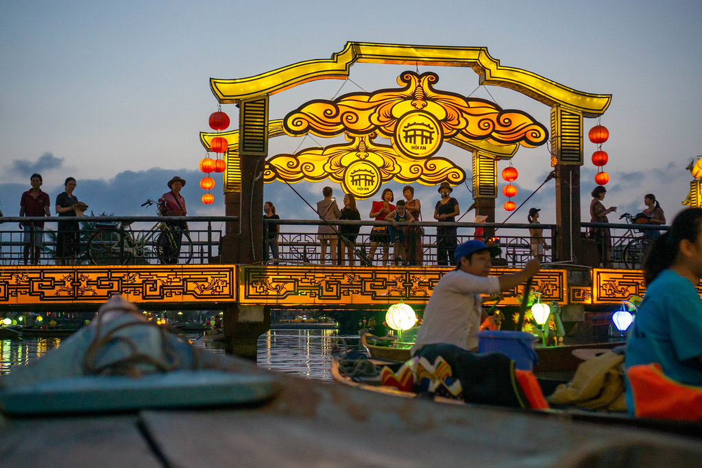 Night Photo from a Wooden Rowing Boat from Tourists standing on the Bridge of Light with Authentic Bright Lanterns in Hoi An, Vietnam