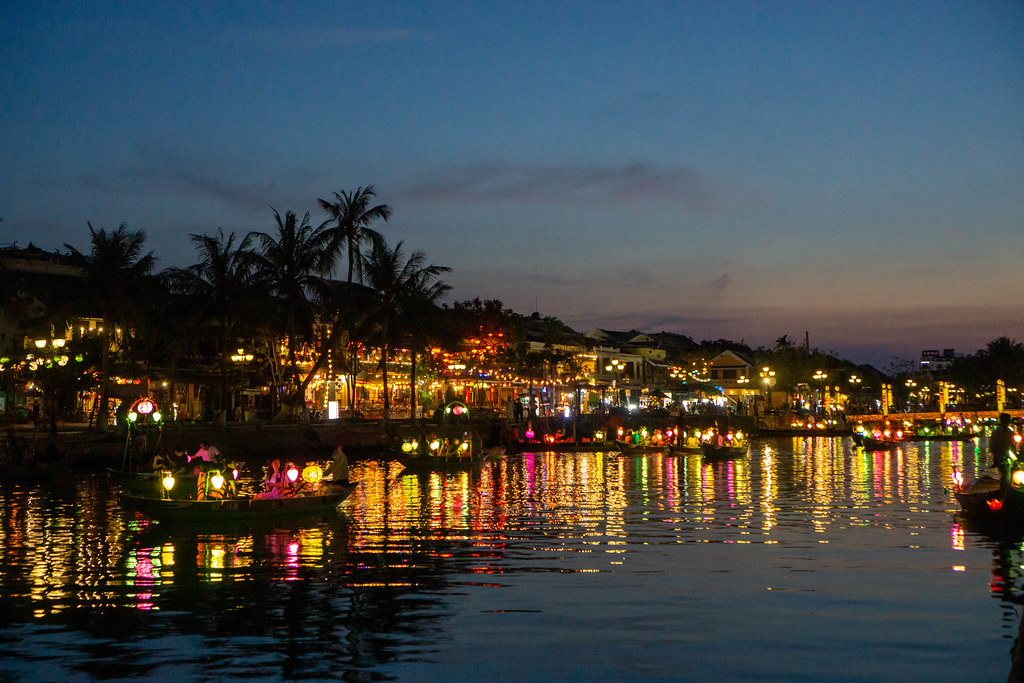 Night Photo of Wooden Rowing Boats with Light Reflection of Lanterns in the Water on a River in the Old Town in Hoi An, Vietnam