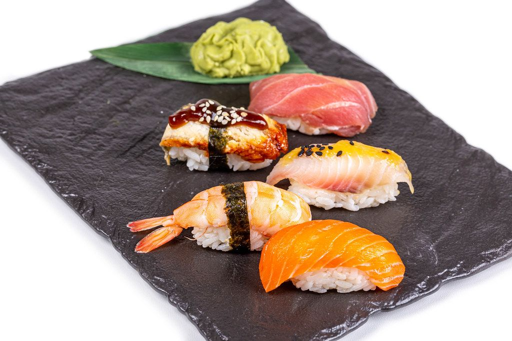 Nigiri with seafood on a black stone tray with wasabi