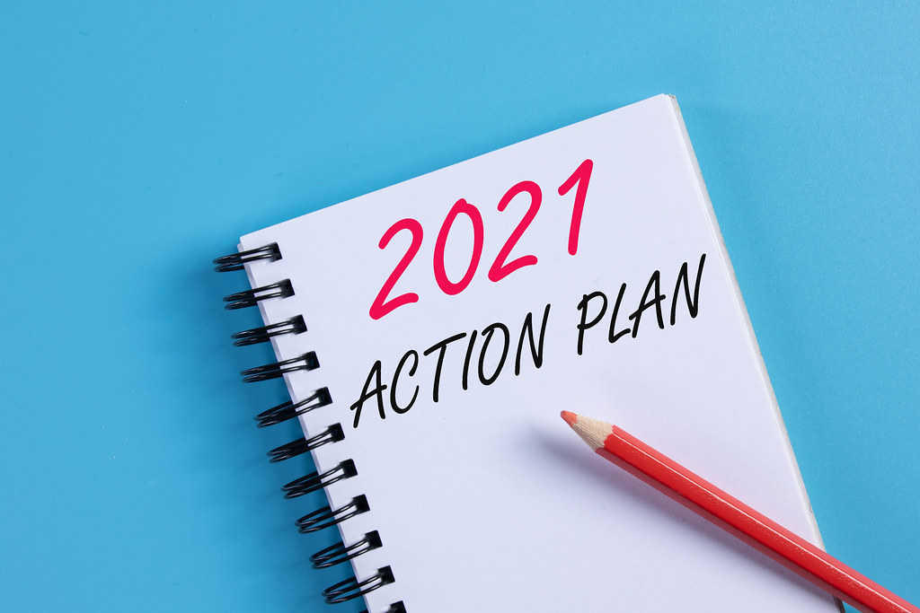 Notebook with 2021 Action Plan text on blue background