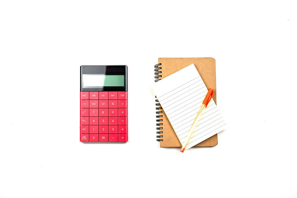Notepad with pen and calculator on the table