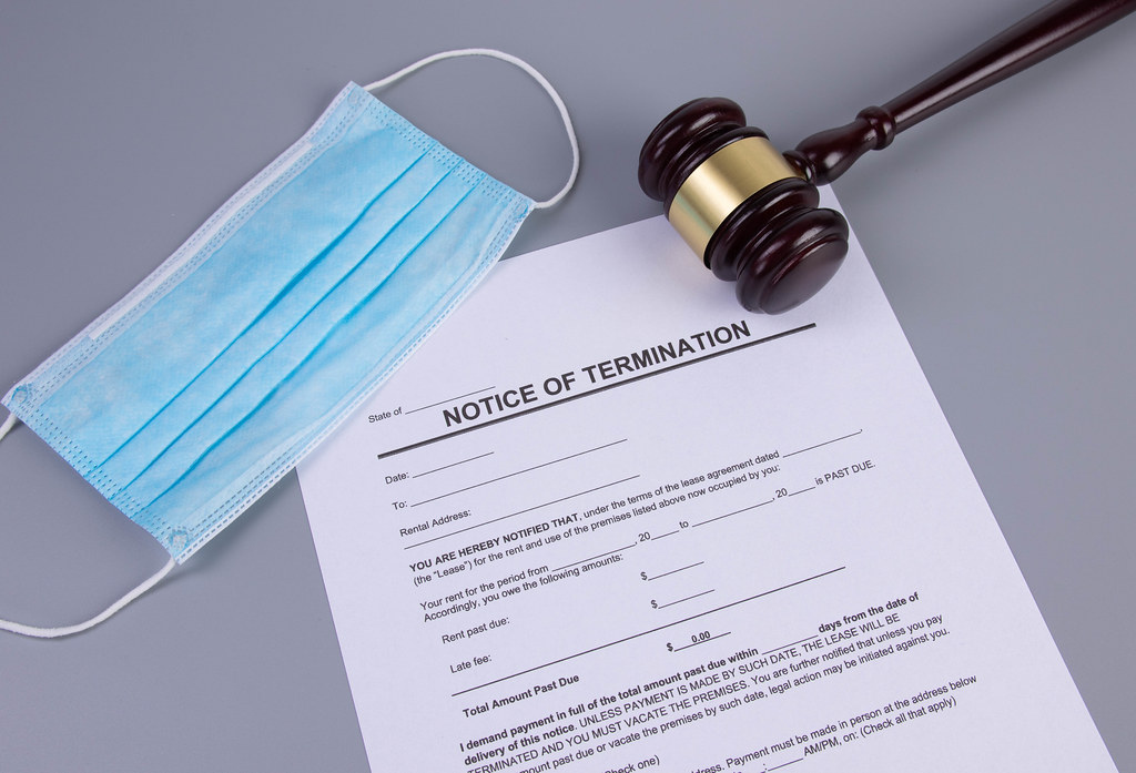 Notice of Termination form with medical face mask and judge gavel