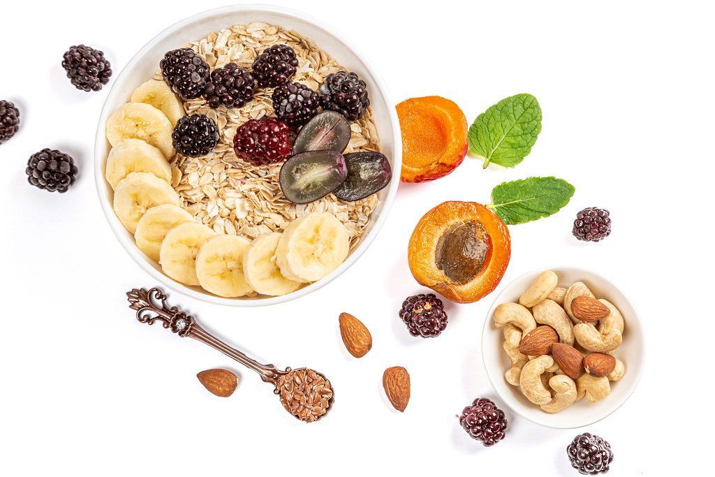 Oat flakes with banana, grapes and blackberries on a white background with apricot, nuts and flax seeds