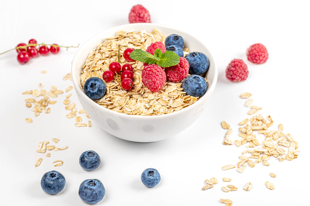 Oat flakes with berries and fresh mint in a bowl and on a white background