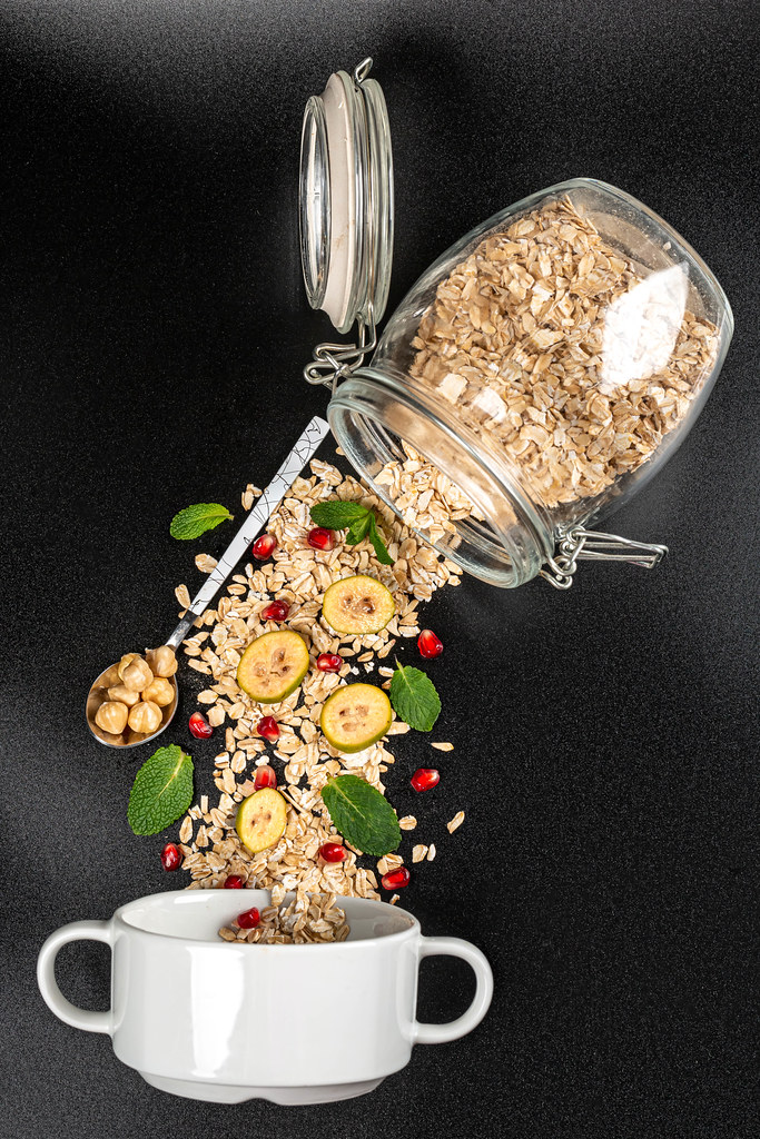 Oat flakes with feijoa pieces, pomegranate, mint and hazelnuts on black background with glass jar and bowl