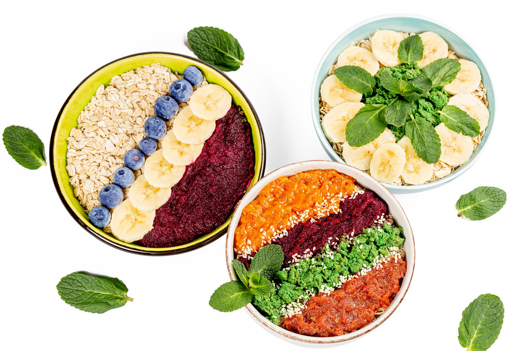 Oat flakes with fresh fruits, berries, mint and fruit purees, healthy food concept