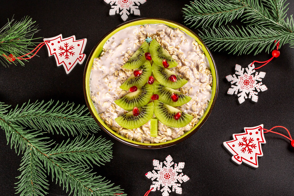 Oat flakes with kiwi, pomegranate and yogurt on a black background with branches of a christmas tree, top view