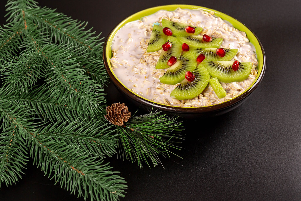 Oat flakes with kiwi, pomegranate and yogurt on a black background with branches of a christmas tree
