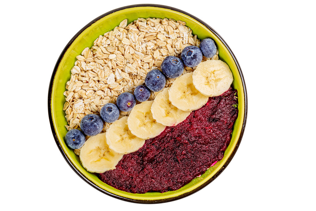 Oat flakes with plum puree, blueberries and banana pieces, top view