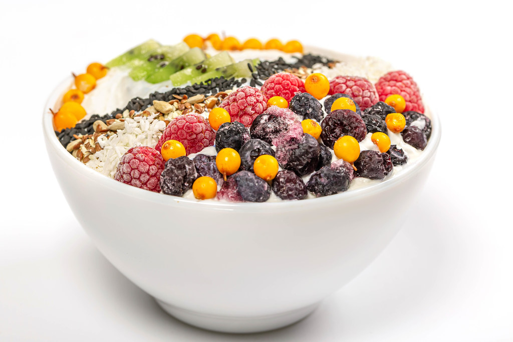 Oat flakes with seeds, berries and coconut flakes in a white bowl, close-up