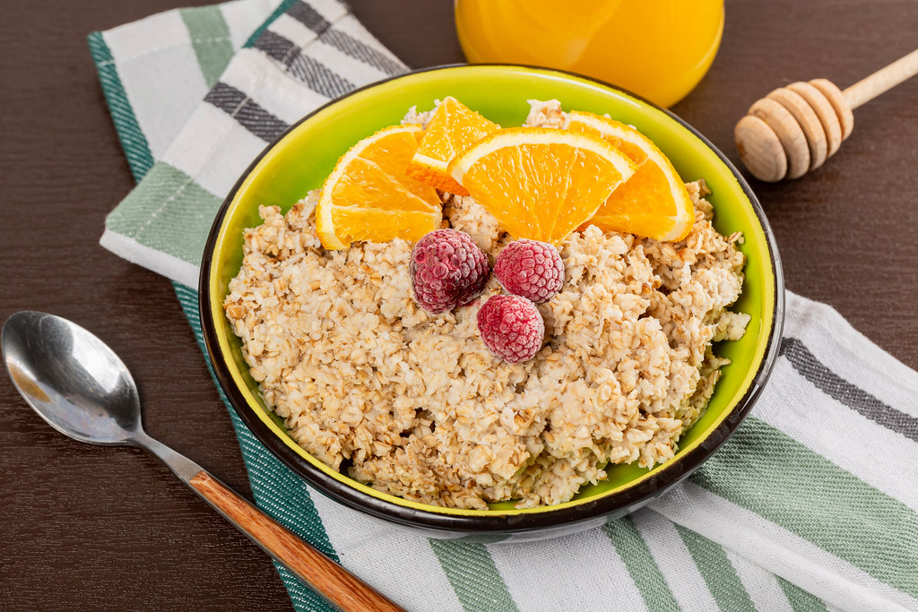 Oatmeal bowl with pieces of orange, raspberry and honey jar