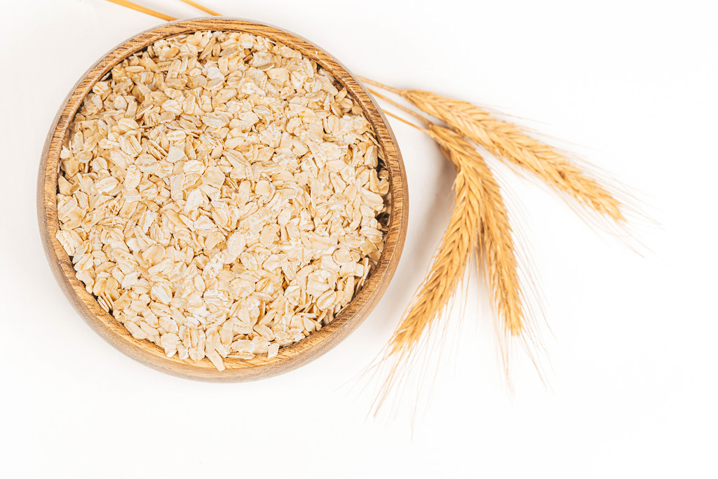 Oatmeal flakes in a round wooden bowl and spikelets on white, top view