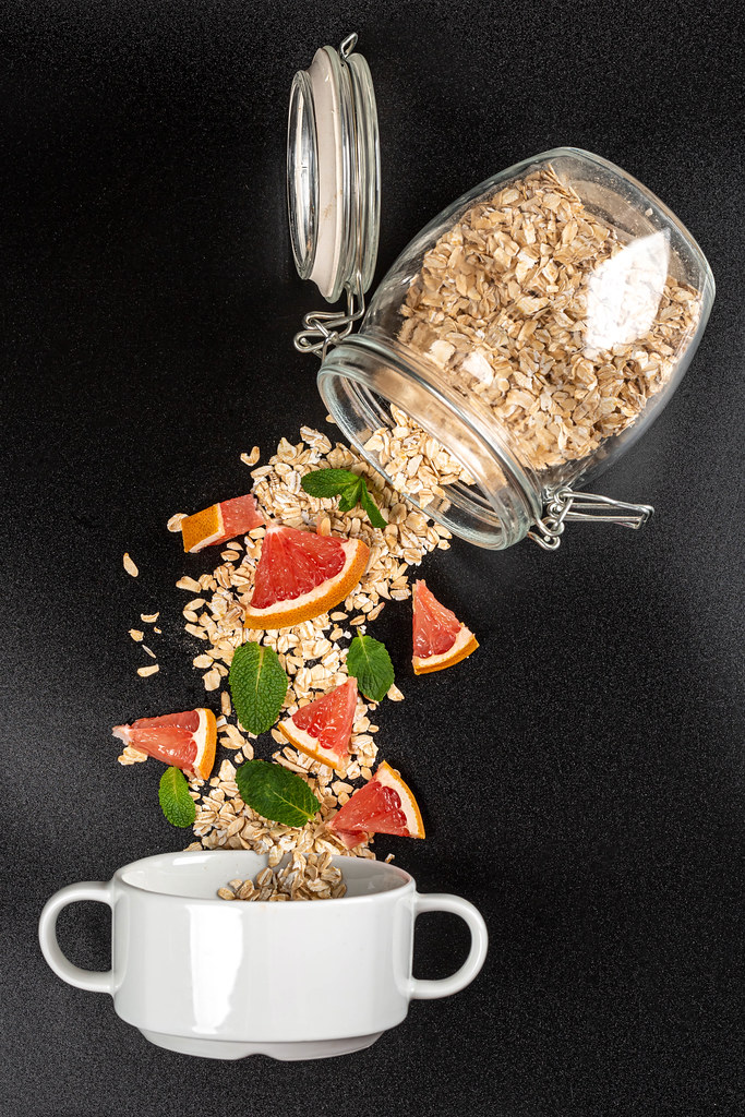 Oatmeal poured from a glass jar with pieces of grapefruit and mint on a dark background with a bowl