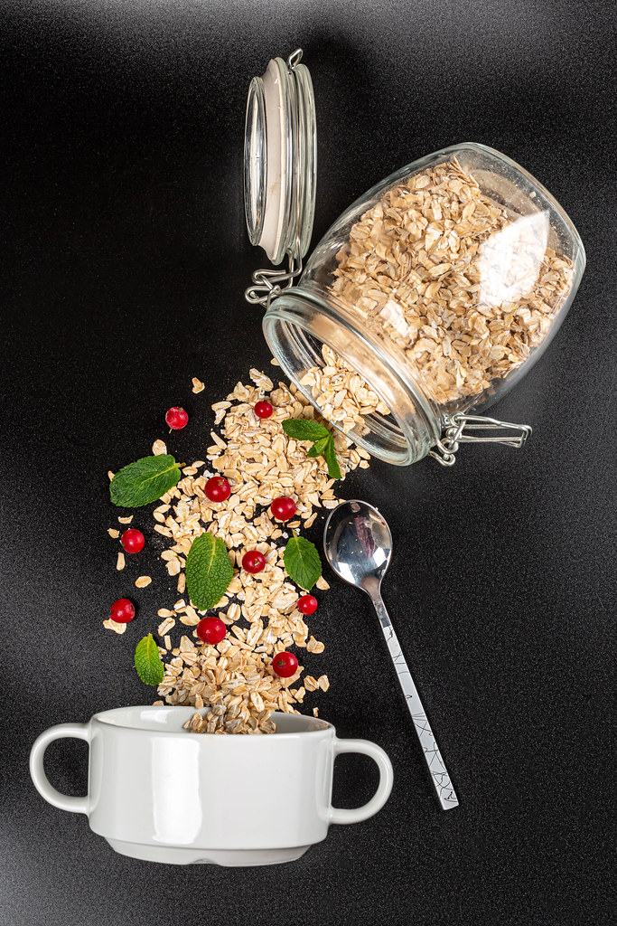 Oatmeal poured from a jar with red currant berries and mint on a black background with a white bowl and spoon