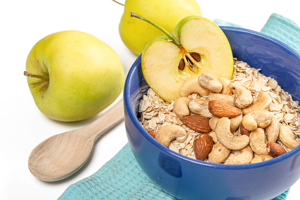 Oatmeal with apple and nuts in a blue bowl, close-up