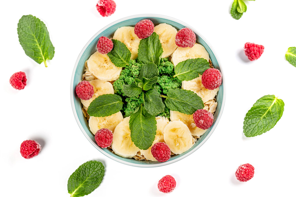 Oatmeal with banana slices, raspberries and mint on white, top view