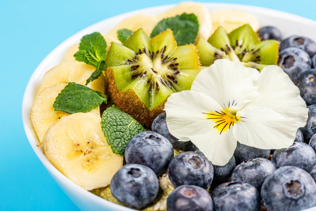 Oatmeal with blueberry, banana, mint, kiwi and white flower on blue background, close-up