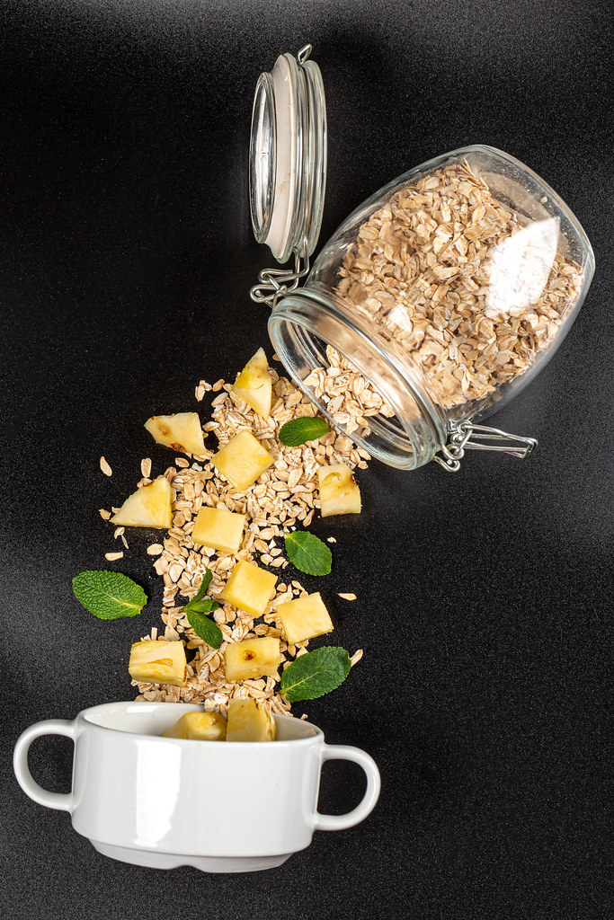 Oatmeal with pineapple pieces and mint leaves poured from a jar on a dark background with a white bowl, top view