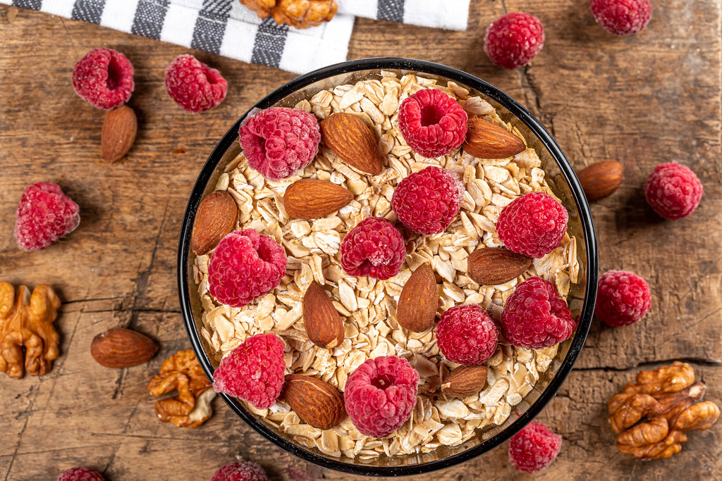 Oatmeal with raspberries and almonds on a wooden background, top view