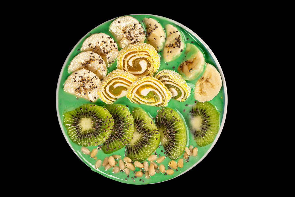 Oatmeal with yogurt, fruits, pine nuts, chia seeds and turkish delight on a black background, top view