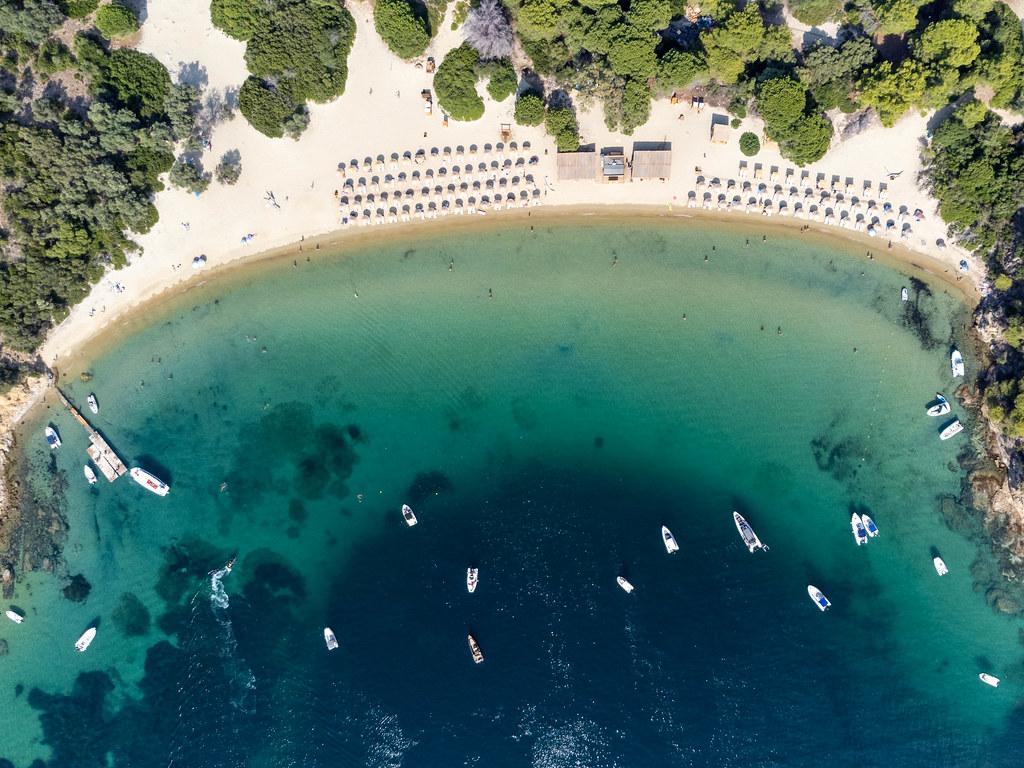 Obene Aufnahme von Sonnenschirmen und Booten auf Tsougria Strand bei Skiathos, Griechenland