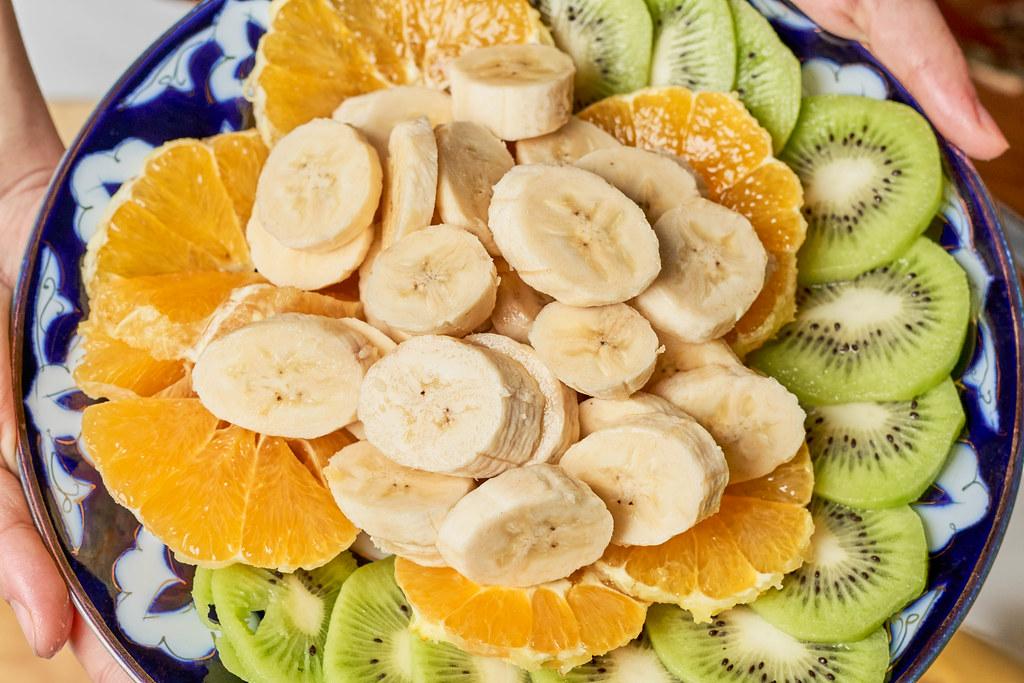 Obstsalat mit Banane, Orange und Kiwi in einer bunten Schüssel: Aufnahme von oben