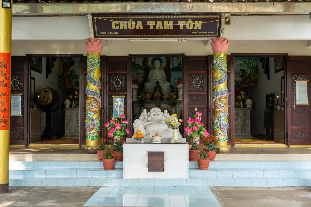 Offerings and Decorations around many different Buddha Statues in front and inside Tam Ton Pagoda at Marble Mountains in Danang, Vietnam