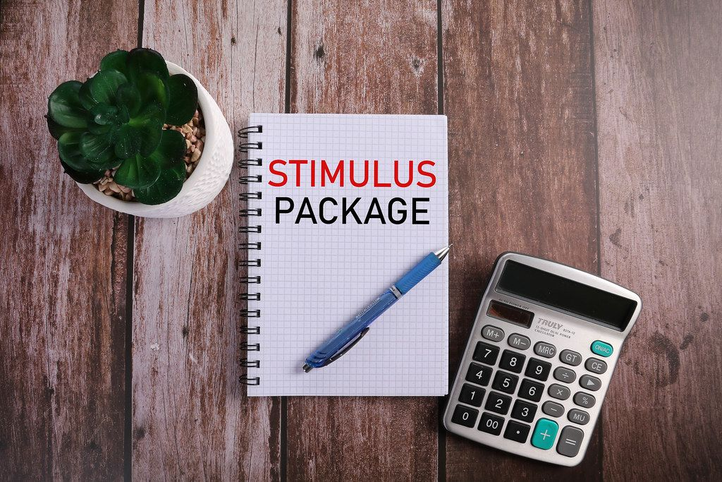 Office desk table with notebook, calculator and Stimulus Package text