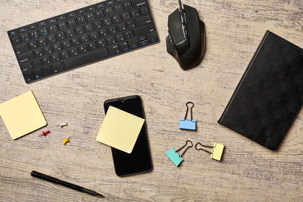 Office workspace with PC keyboard, mouse, notepad and smartphone