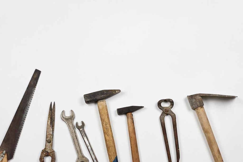 Old and rustic handy working tools on the white background