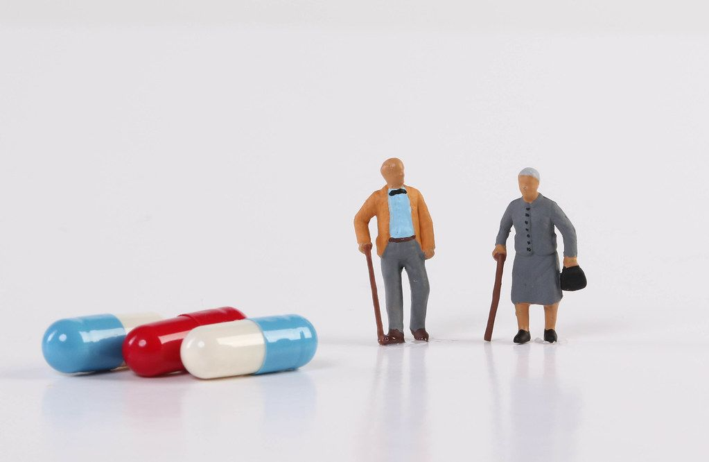 Old couple figures with pills on white background