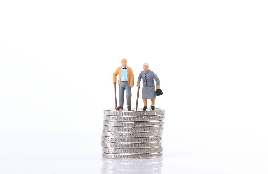 Old couple standing on top of stack of coins on white background