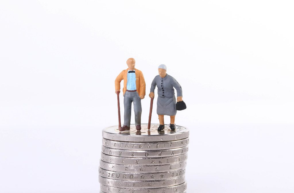Old couple standing on top of stack of coins