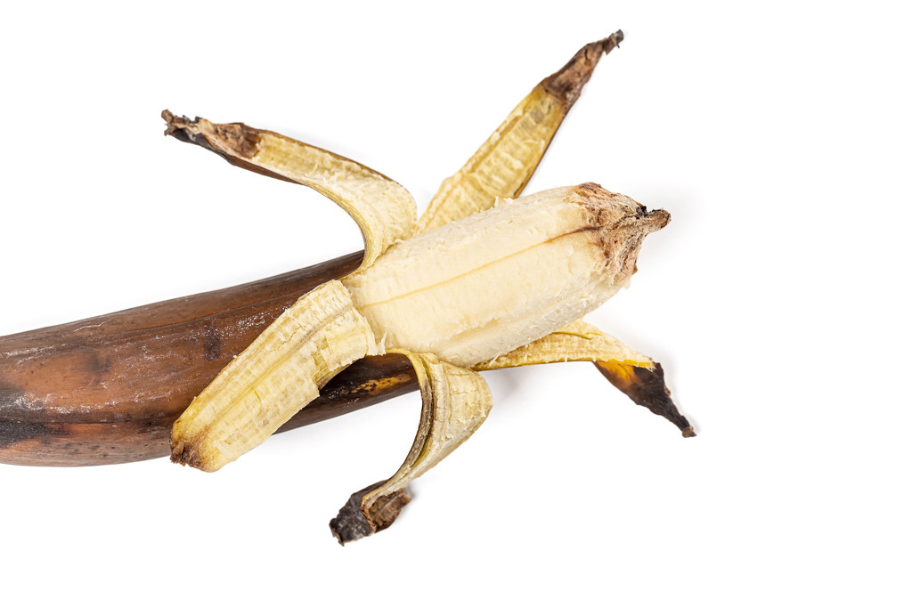 Old dark brown banana on background